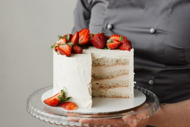 Mädchenkellner, der ein tablett mit einem weißen kuchen hält, der mit erdbeeren verziert wird