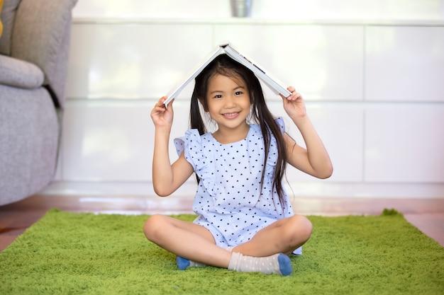 Mädchenkind, das buch auf kopfspiel hält und im wohnzimmer sitzt