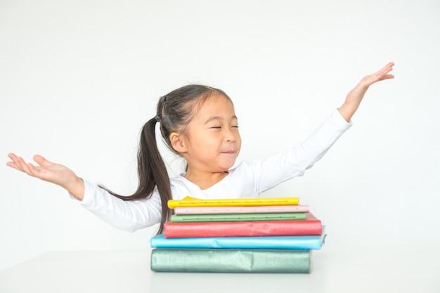 Mädchenkind hob die hände hoch, die ihre schule studierend hausaufgaben feiern, beendete schließlich