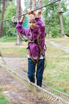 Mädchenkind im abenteuer, das hochseilpark klettert