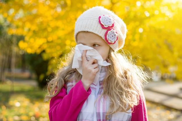 Mädchenkind mit kalter rhinitis auf herbsthintergrund