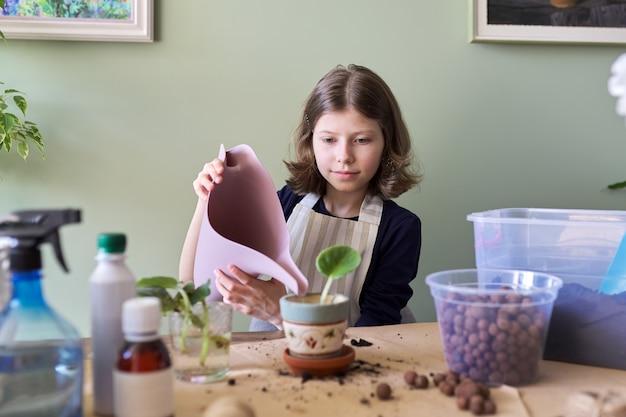 Mädchenkind pflanzt blatt der jungen pflanze von saintpaulia im topf. verwendet spachtel, gießkanne, boden. neue pflanze im haus, pflege, hobby, zimmerpflanze, topffreunde, kinderkonzept