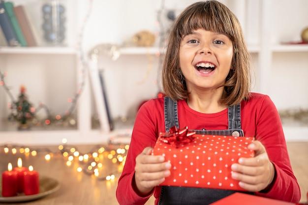 Mädchenkind überraschtes glückliches gesicht in der weihnachtszeit