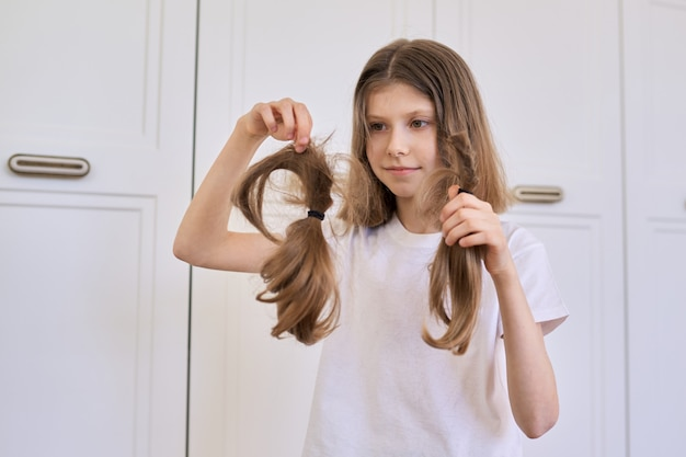 Mädchenkind zeigt getrimmtes haar, friseur zu hause, kopienraum.