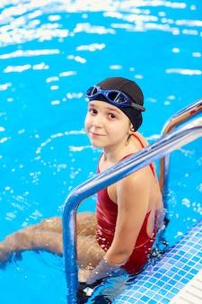 Mädchenkinderschwimmer in einem roten badeanzug auf hintergrund