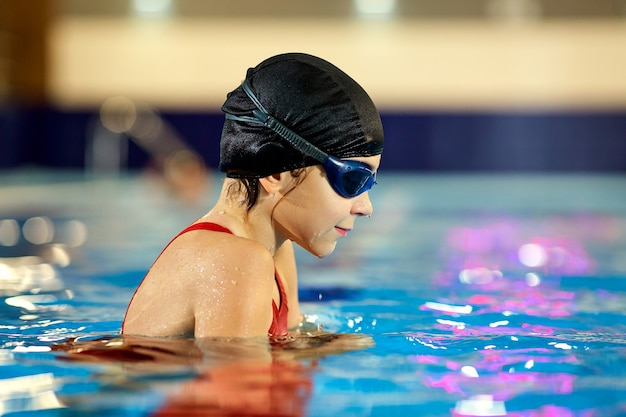 Mädchenkindschwimmer in einem roten badeanzug auf hintergrund