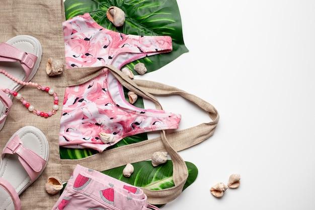 Mädchenkleidung und accessoires auf weißem hintergrund mit blättern und muscheln flach draufsicht sommer...