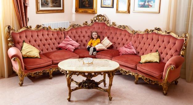 Mädchenkleinkind in einem wohnzimmer mit barockem dekor.