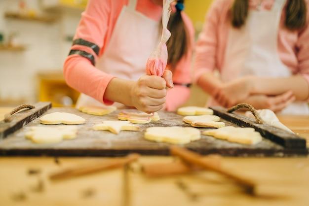 Mädchenköche, die vorbereiten, kekse in den ofen zu senden