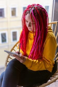 Mädchenkünstler, illustrator zeichnet in notizbuch, macht skizzen. nahaufnahme der frau mit rosa dreadlocks
