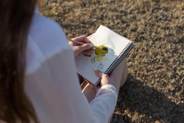Mädchenkünstler malt ein bild mit aquarellen in der natur.