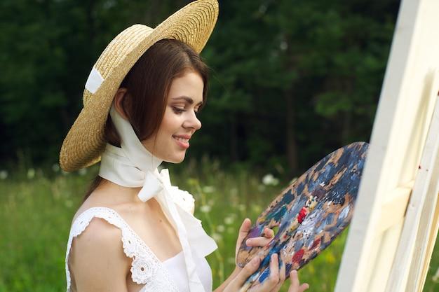 Mädchenkünstlerin mit einer palette in ihren händen zeichnet ein bild in einem schönen hut