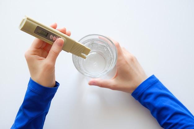 Mädchenlabor bestimmt wasserqualitätskontrolle. in den händen eines digitalen testers.