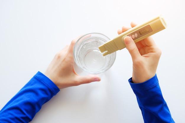 Mädchenlabortechniker hält einen digitalen prüfapparat an, um wasserqualitätskontrolle festzustellen.