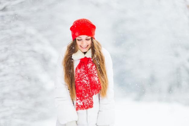 Mädchenlächeln in einem verschneiten park, der warme winterkleidung trägt