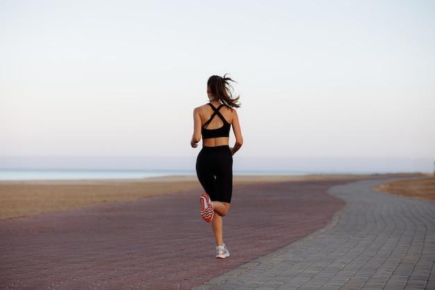 Mädchenläufer in einem schwarzen trainingsanzug und in turnschuhen läuft durch das meer während des sonnenuntergangs