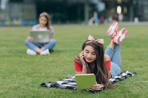 Mädchenlesebuch im park, sitzend auf gras und rest im universitätsgelände habend. hörende musik der frau durch kopfhörer und lesebuch im park