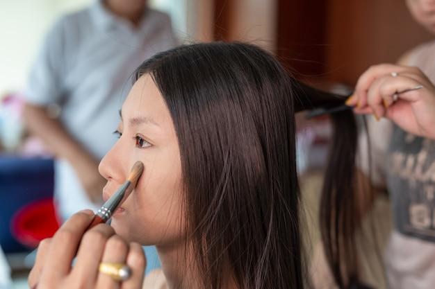 Mädchenmake-up durch die verwendung eines professionellen maskenbildners.