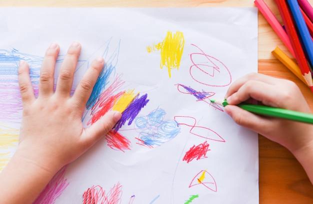 Mädchenmalerei auf papierblatt mit farbbleistiften auf dem kind des holztischs zu hause, das zeichnungsbild und bunten zeichenstift tut