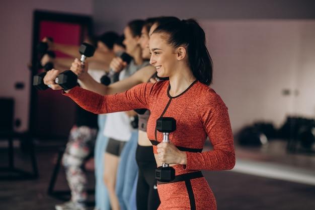 Mädchenmannschaft, die zusammen aerobic im fitnessstudio ausübt