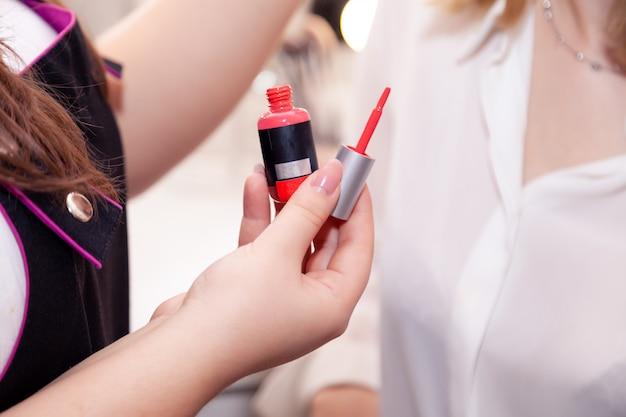 Mädchenmaskenbildner, visagiste, modell, das roten flüssigen lippenstift hält, erröten, rouge. anzeige keine marke dekorative professionelle kosmetikgeschäft