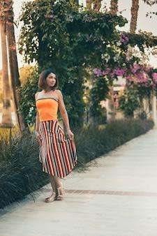 Mädchenmodell, das unter palmen im urlaub in den tropen aufwirft. urlaub in einem warmen land am meer.