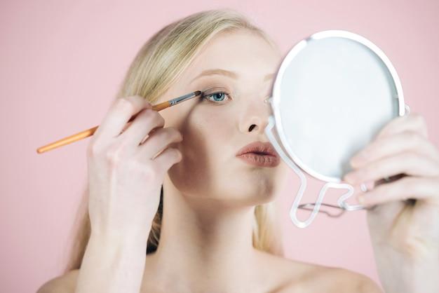Mädchenmodell mit make-upbürste nahe gesicht. hautpflegeprodukte. frau mit blauen augen, die make-up mit make-up-pinsel auftragen und in den spiegel schauen. leichtes make-up. natürliche schönheit. gesichtsbehandlungskonzept hautpflege
