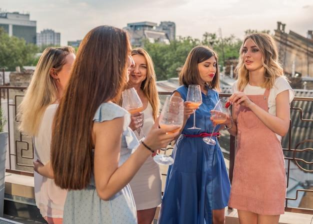 Mädchenparty auf dem balkon. schöne freundinnen, die spaß an der junggesellenabschied haben. sie feiern und trinken champagner beim junggesellinnenabschied