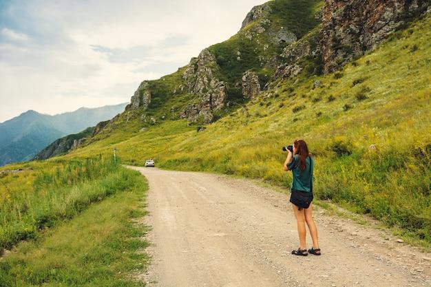 Mädchenphotographie mit kamera auf gebirgsstraße, ansicht von der rückseite.