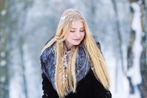 Mädchenporträt des jungen jugendlich des winters. schönheits-frohes vorbildliches girl, das spaß im winterpark lacht und hat