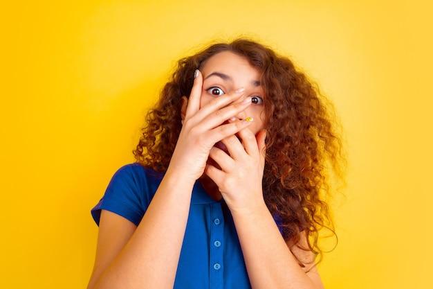 Mädchenporträt des kaukasischen teenagers auf gelb