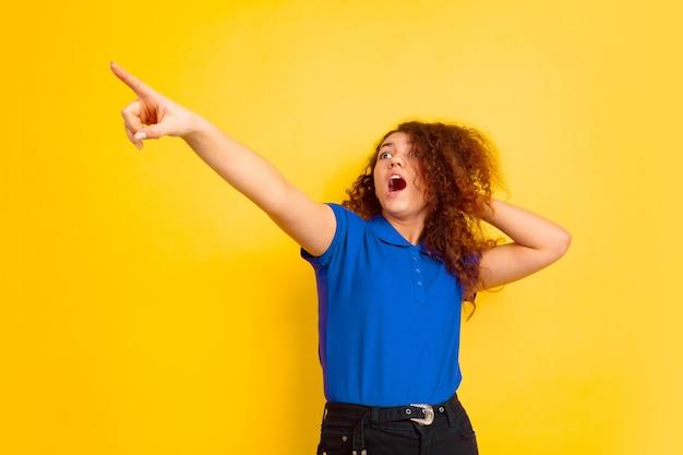 Mädchenporträt des kaukasischen teenagers auf gelber wand