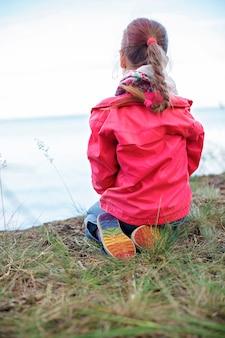 Mädchenpower und toleranz. hübsches mädchen in der rosa jacke und in den schuhen mit regenbogenfarbenem boden, die am ufer des meeres sitzen und über den horizont hinaus schauen, konzentrieren sich auf den bunten teil der schuhe