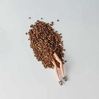 Mädchenpuppenbeine, die von einem haufen kaffeebohnen auftauchen