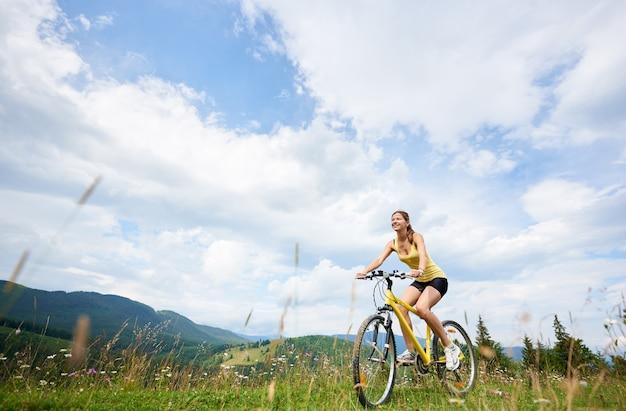 Mädchenradfahrer, der auf gelbem mountainbike reitet