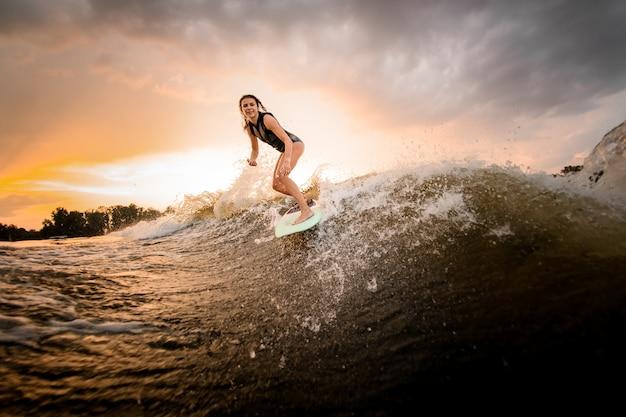 Mädchenreiten auf dem wakeboard auf dem fluss auf der welle