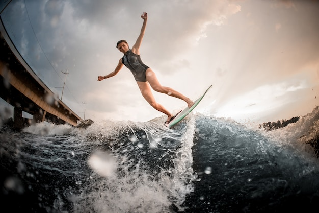 Mädchenreiten auf dem wakeboard auf dem fluss im hintergrund der steigenden hände der brücke