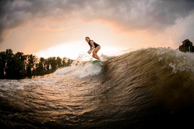 Mädchenreiten auf dem wakeboard auf dem fluss