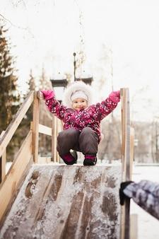 Mädchenreiten mit hölzerner achterbahn, winter und spaß