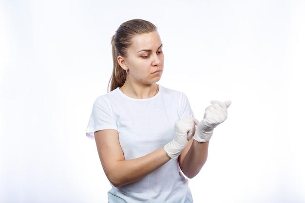 Mädchensanitäter zieht weiße medizinische handschuhe an den händen an. schutz vor keimen und viren. sie trägt ein weißes t-shirt auf weißem hintergrund.