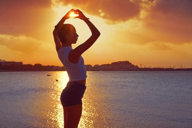 Mädchenschattenbild an der strandsonnenuntergang-herzform
