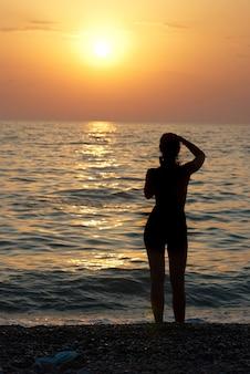 Mädchenschattenbild und sonnenuntergang auf dem meer