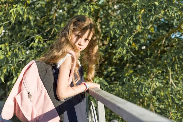Mädchenschulmädchenblondine mit rucksack in der schuluniform nahe zaun im schulhof