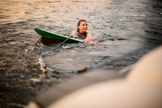 Mädchenschwimmen, welches das wakeboard und ein seil des motorboots hält