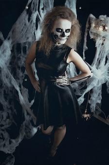 Mädchenskeletthexe, die in den netzen, halloween aufwirft. hexe bereitet sich auf die feiertagsnächte der toten vor