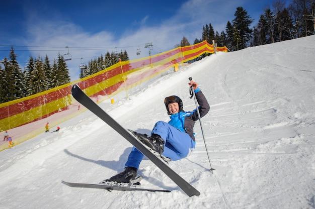 Mädchenskifahrer nach dem fall auf berghang. skigebiet