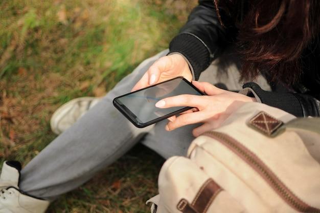 Mädchentourist sitzt und sucht nach einem weg mit dem gps-navigator auf dem smartphone allein im wald