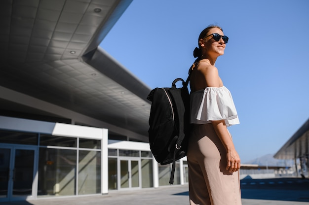 Mädchentouristin mit schwarzem rucksack und sonnenbrille