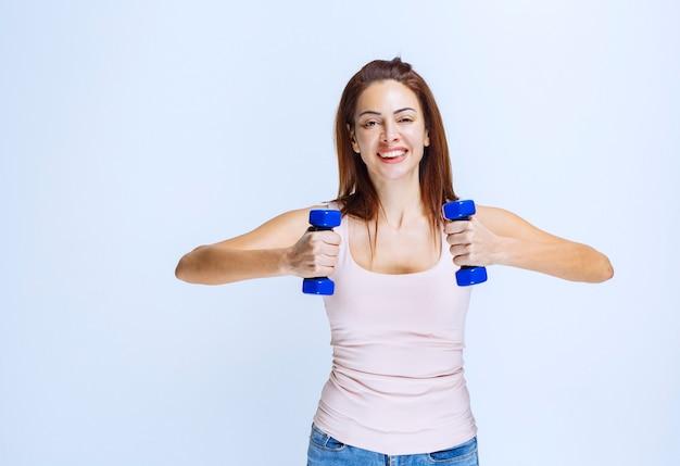 Mädchentraining mit blauen hanteln und anheben in paralleler position.