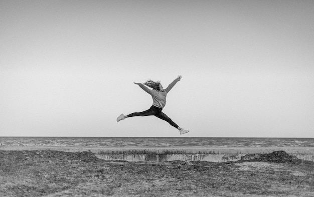 Mädchenturnerin, die auf dem hintergrund des meeres springt
